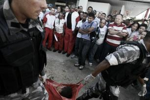 Two young men allegedly criminals were persecuted and killed by more than 20 cops of four elite military police groups in Avenue ACM in Salvador, Bahia. In the photo: Cops removing the bodies of the two unidentified youths on the pretext that they are providing assistance after an exchange of gunfire, although they are already dead. By law, police could not remove the bodies before the crime scene investigation to prove the circumstances of death. December 3, 2010.