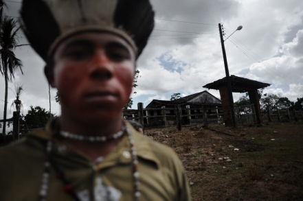A Pataxó indian stands in front of the Rancho Alegre ranch abandoned by its non-indian owners after a long conflict, in Pau Brasil, southern Bahia state. REUTERS / Lunae Parracho