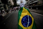 A demonstrator wears a Guy Fawkes mask and a Brazilian flag during a protest on the streets near the Maracana stadium in Rio de Janeiro June 30, 2013. REUTERS / Lunaé Parracho